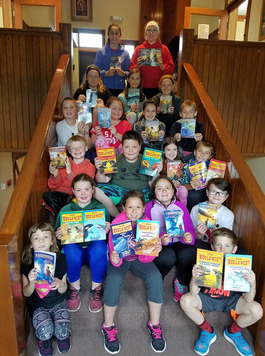 Students posing with their Scholastic book fair books