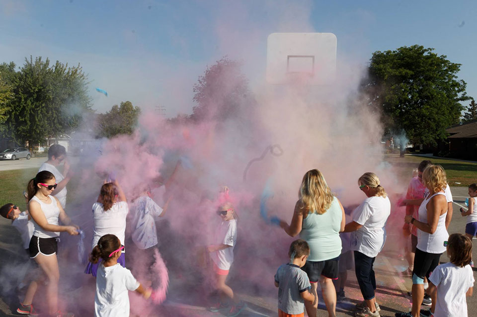 Staff and students playing with chalk during the color run