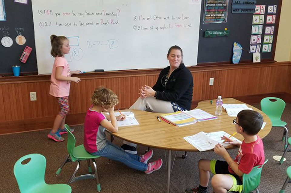 Mrs Eichmeier sitting with students while they learn