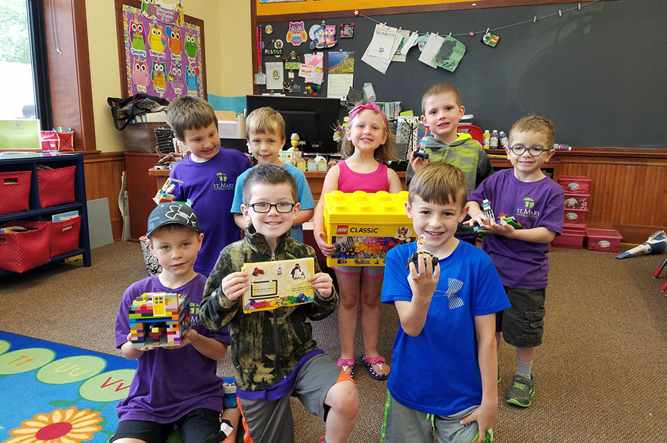 Student posing with their lego creations