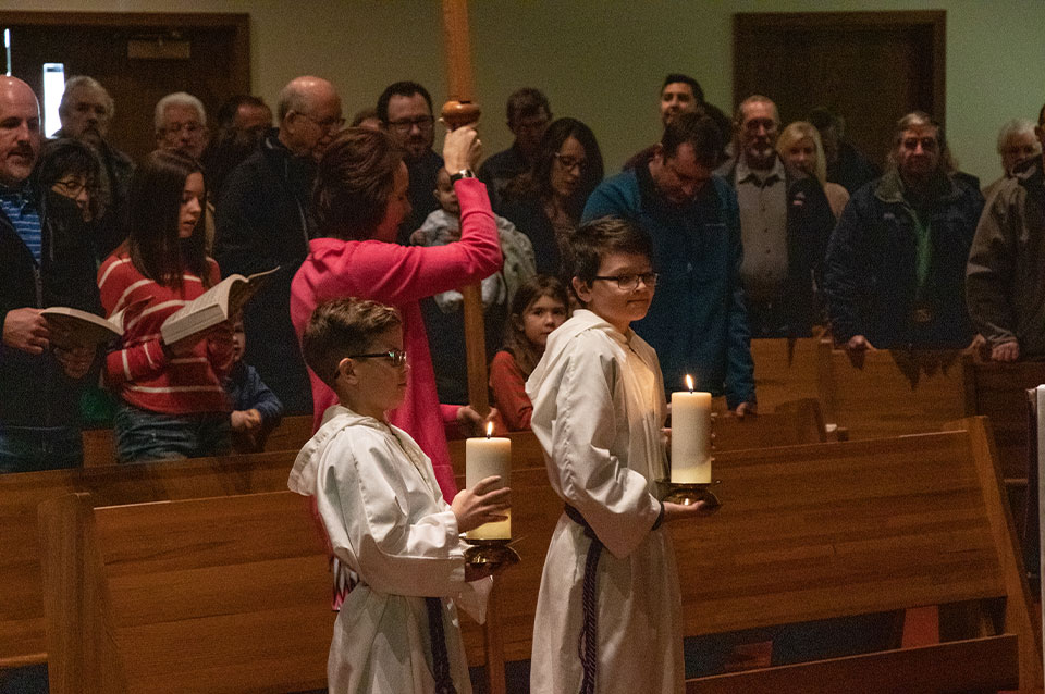 6th graders holding candles while serving at mass